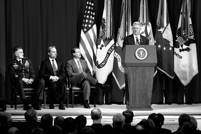 980217-D-9880W-094 President Bill Clinton addresses an audience of military personnel and civilian Department of Defense employees at the Pentagon on Feb. 17, 1998. The internationally televised speech, in part a warning to Saddam Hussein, was in essence an explanation to the American people of why military action may be required against Iraq. Listening to the address from the stage are Chairman of the Joint Chiefs of Staff Gen. Henry H. Shelton (left), U.S. Army; Secretary of Defense William S. Cohen (center) and Vice President Al Gore (right). DoD photo by R. D. Ward.